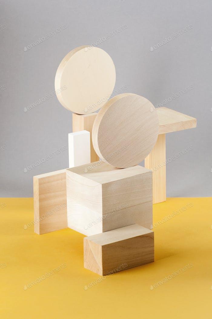 Abstraktion von geometrischen Holzfiguren auf einem grau-gelben Hintern