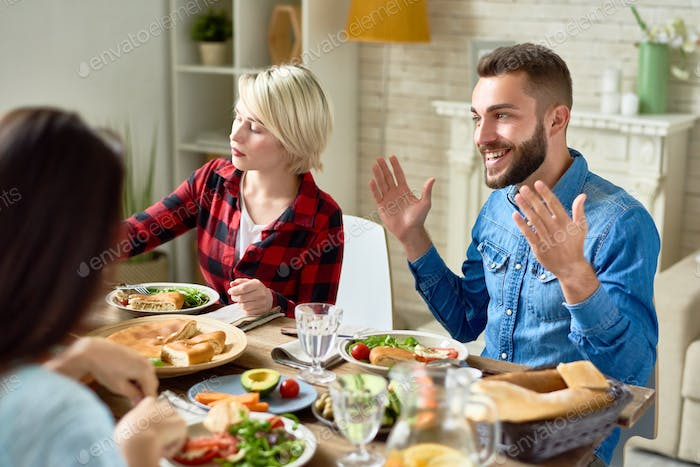 Happy Man Telling Stories at Dinner Table
