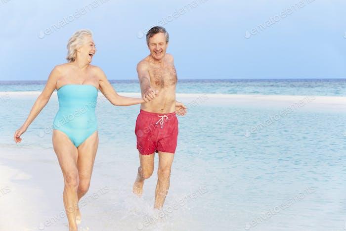 Seniorenpaar Splashing In Schönen Tropischen Meer
