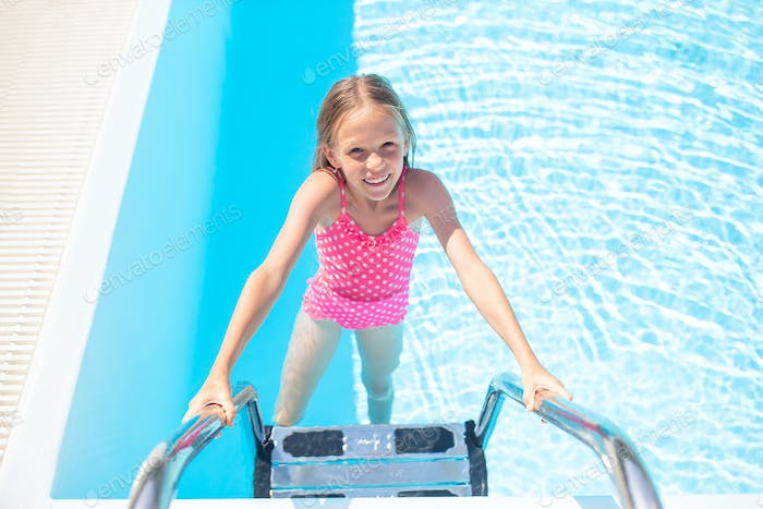 Adorable little girl swimming at outdoor swimming pool