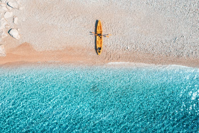 Aerial view of sandy beach with colorful canoes and blue sea