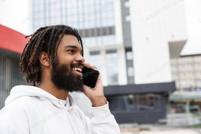 Cheerful happy young man talking by mobile phone