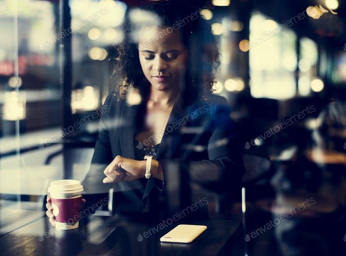 Woman looking at her watch at cafe