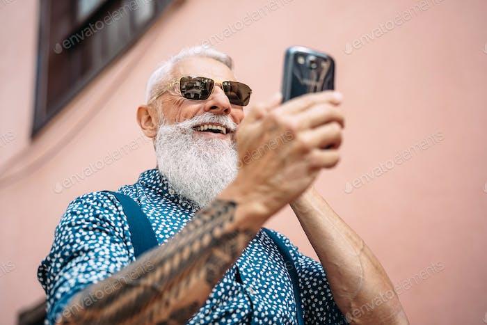 Happy senior man messaging on mobile smartphone outdoor