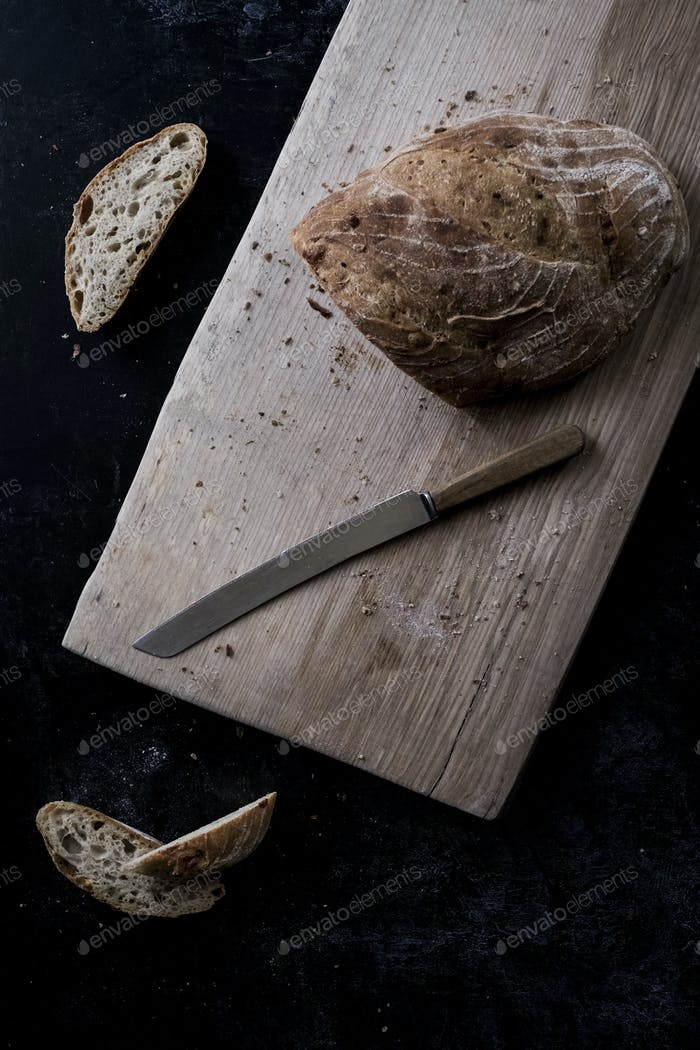 A loaf of brown bread on a board and a bread knife