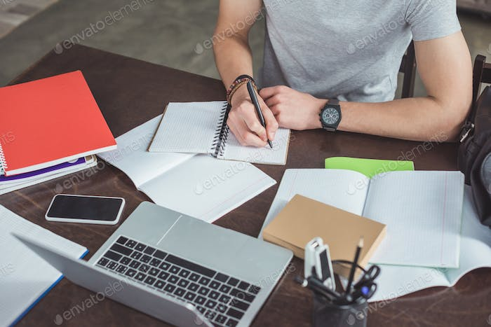 partial view of student writing in copybook while sitting at table with laptop and smartphone