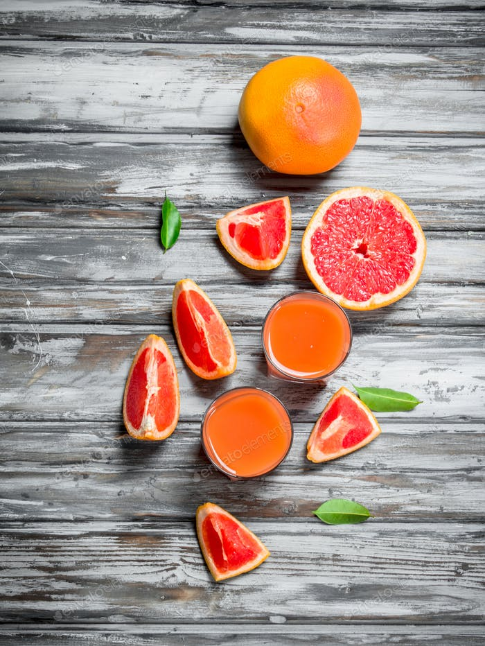Grapefruit juice in a glass and pieces of fresh grapefruit.