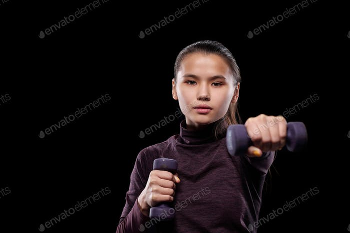 Active sporty girl with dumbbells stretching arm forwards in front of camera
