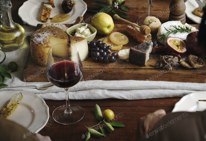 People eating a platter of cheese with seasonal fruits and wine
