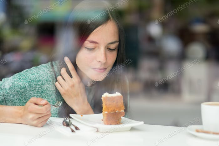 young pretty woman eating a cake