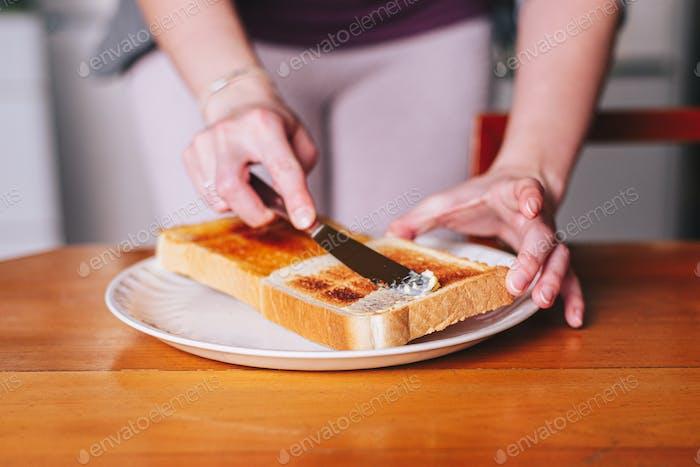 zwei Hände Butter auf Toast verteilen