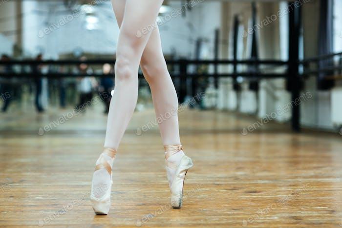 Female legs in pointe shoos standing on toes