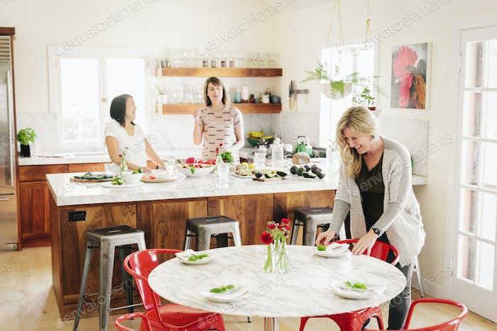 Three women in a kitchen preparing lunch.