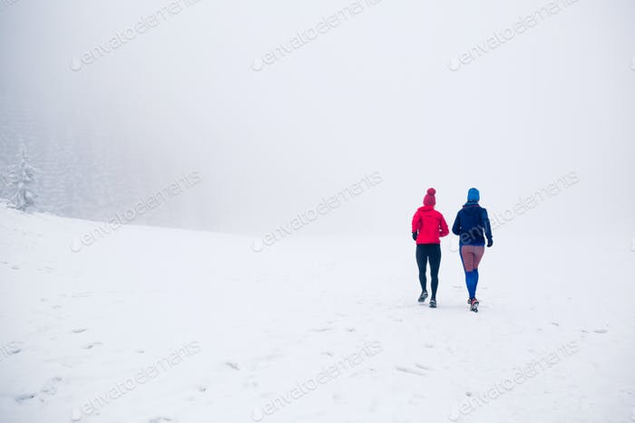 Two women trail running on snow in winter mountains