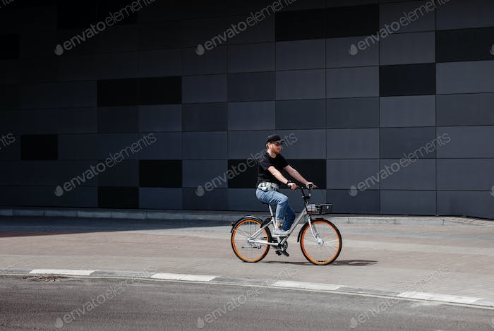 Stylish guy dressed in trendy jeans clothes rides bicycle in the street against the background of a