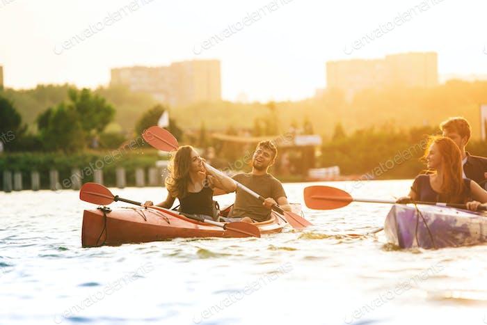Glückliche Freunde Kajakfahren auf dem Fluss mit Sonnenuntergang auf dem Hintergrund