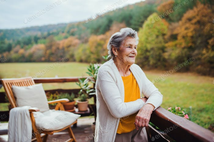 An elderly woman standing outdoors on a terrace on a sunny day in autumn.