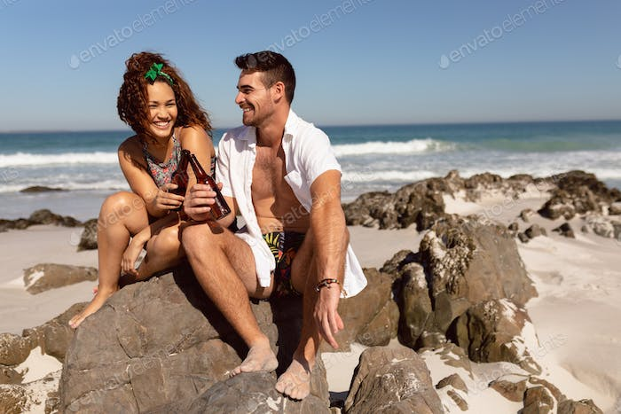 Front view of happy young Mixed-race couple toasting beer bottle on beach in the sunshine