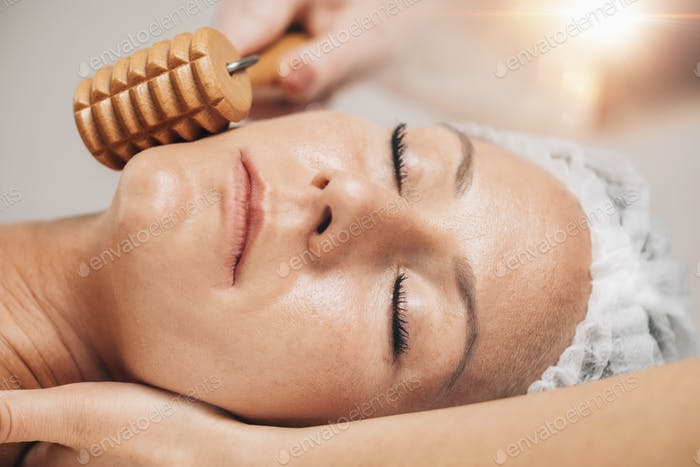 Maderotherapy Face Massage with Wooden Roller. Reducing Wrinkles and Sagging Cheeks
