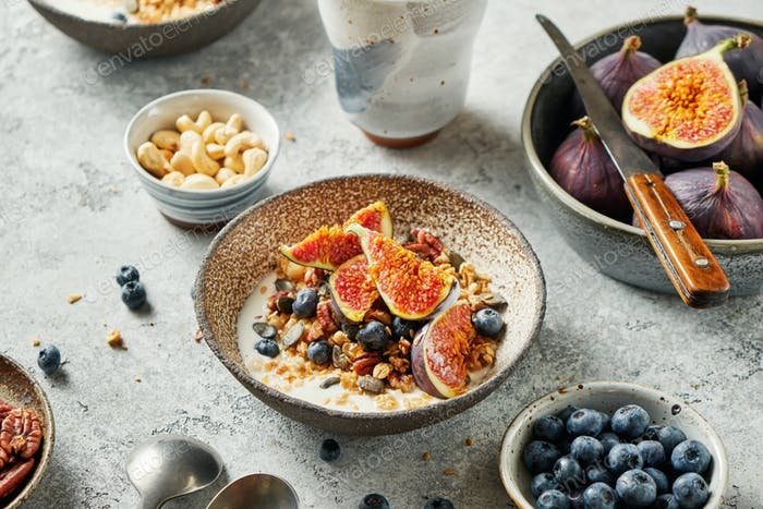 Cereal breakfast with fresh berries, seeds and figs in bowl