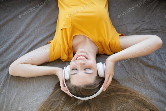 Lächelnde junge Dame in Kopfhörern Musik hören oder Audio buch auf ihrem Bett, Blick über den Kopf