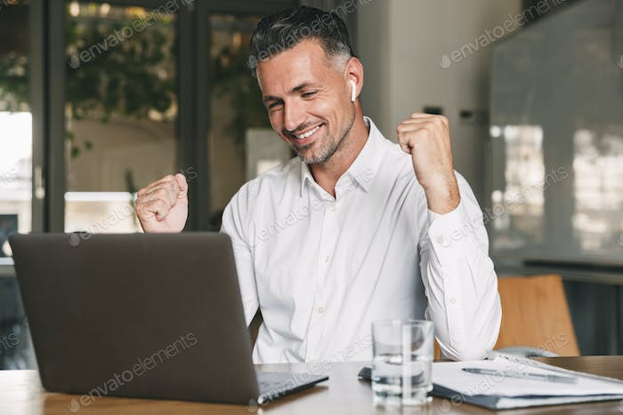 Photo of happy businessman 30s wearing white shirt and wireless