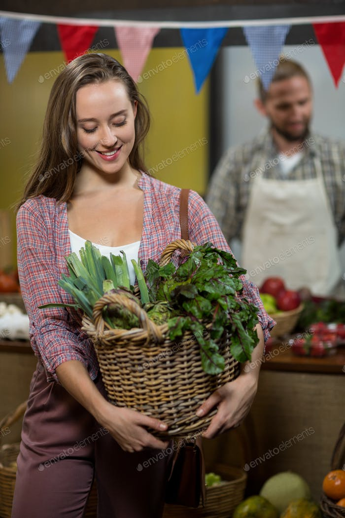 Woman holding basket of green leafy vegetables in the grocery store