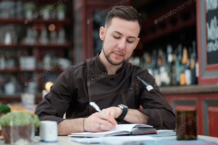 Caucasian male chef cook thinking about new menu or recepts.