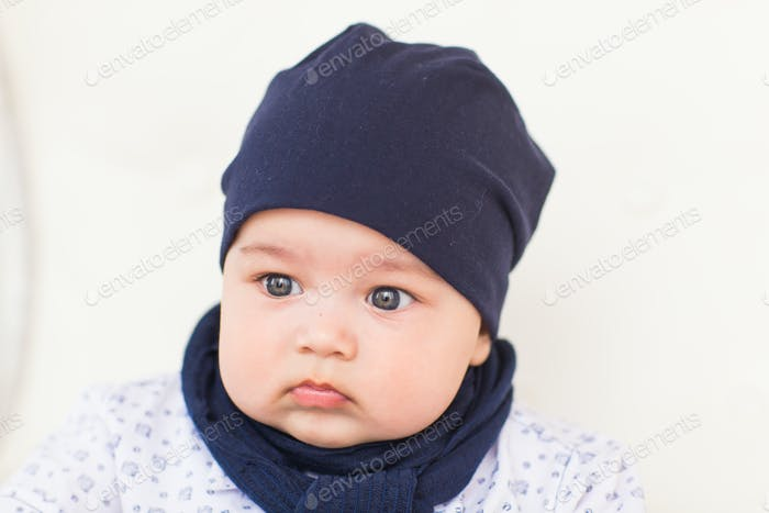 Close up portrait of cute baby boy wearing blue hat.