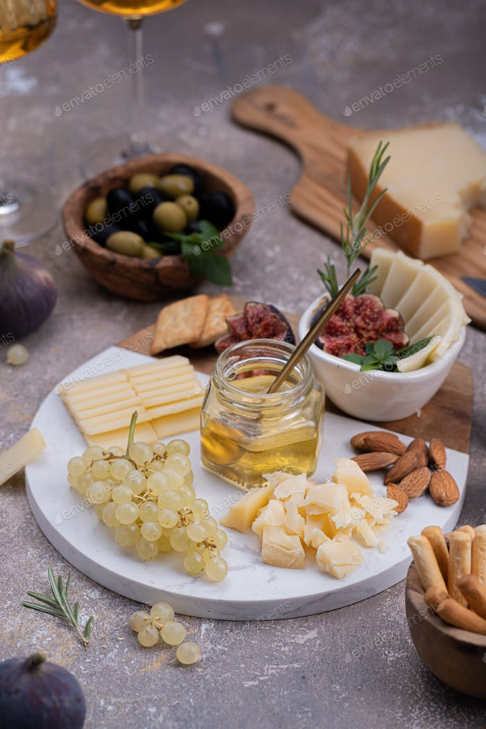 Marble Cheese board with delicous cheeses, nuts, honey and grapes