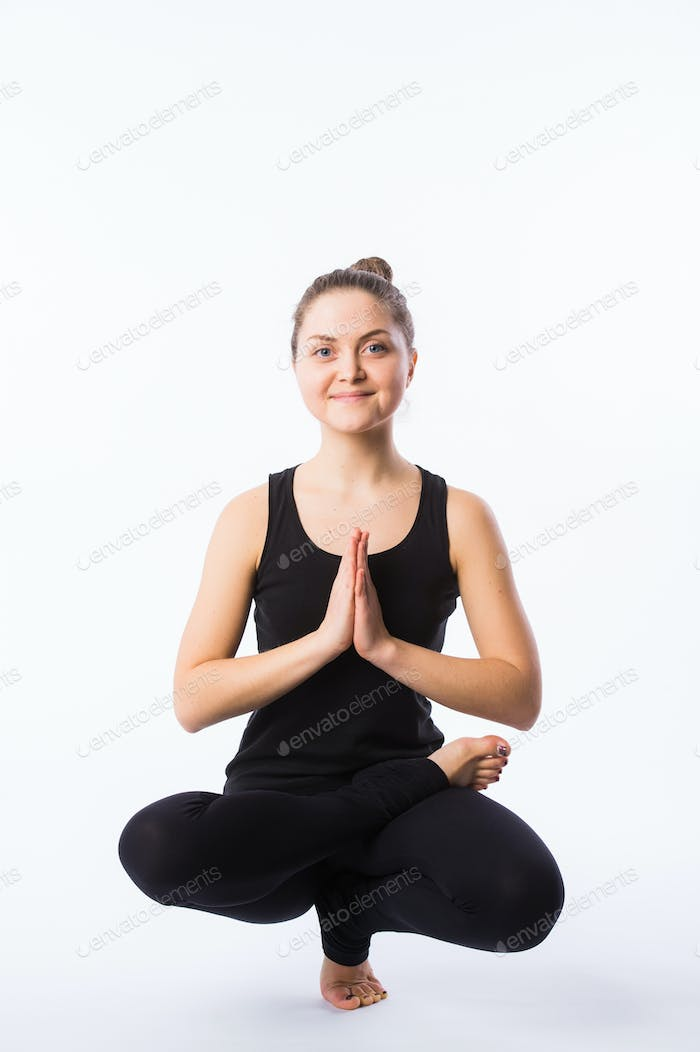 Sporty yoga girl on white background sitting in squatting position with Anjali mudra
