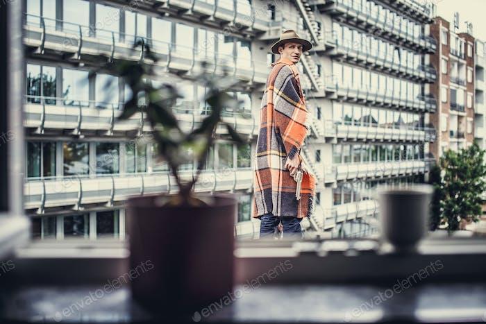 Mann in Decke auf Mehrfamilienhaus Hintergrund.