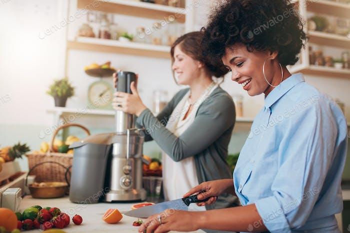 Zwei Frauen, die Fruchtsaft im Café zubereiten