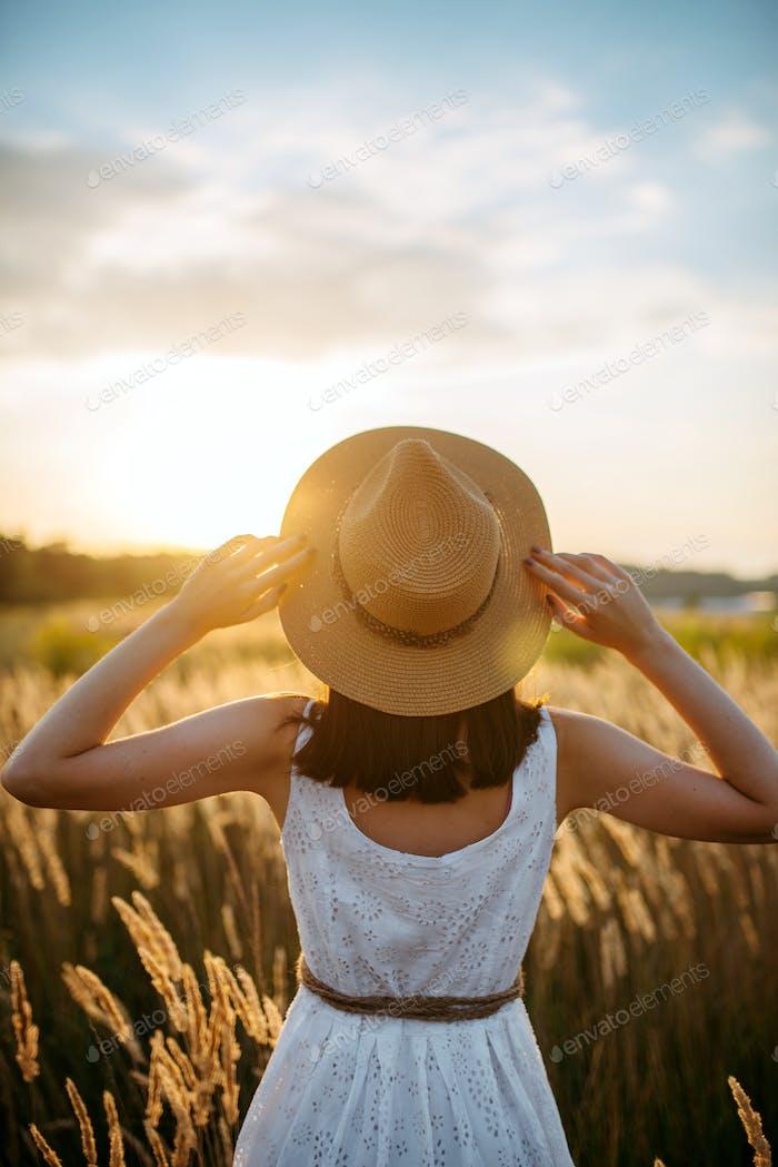 Woman in dress walking in wheat field on sunset