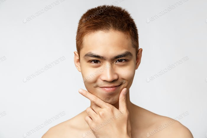 Beauty, skincare and men health concept. Headshot of smart and creative asian young man standing