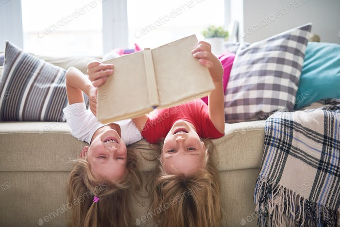 Sisters Reading Book Upside Down