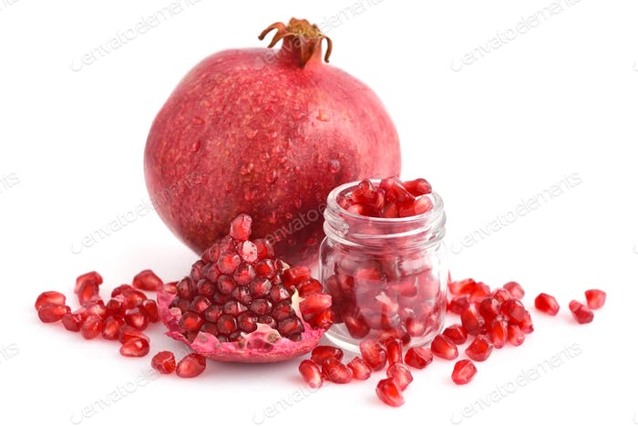 Pomegranate fruit and glass jar with seeds isolated on white bac