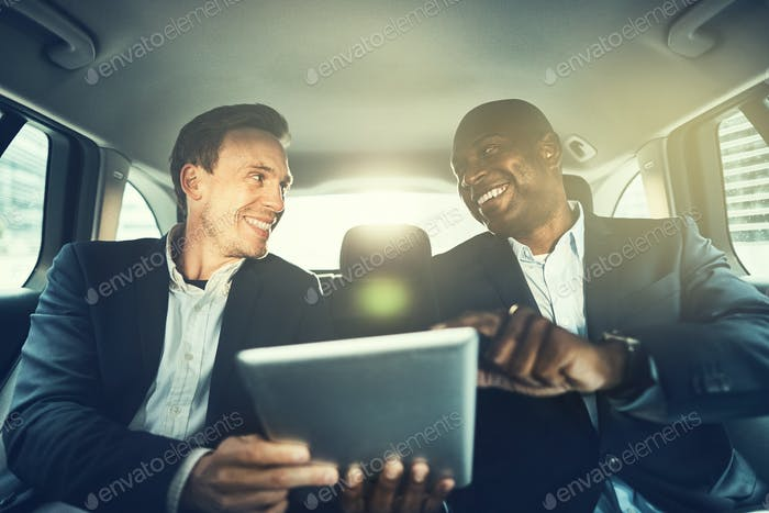 Business colleagues working online in the backseat of a car