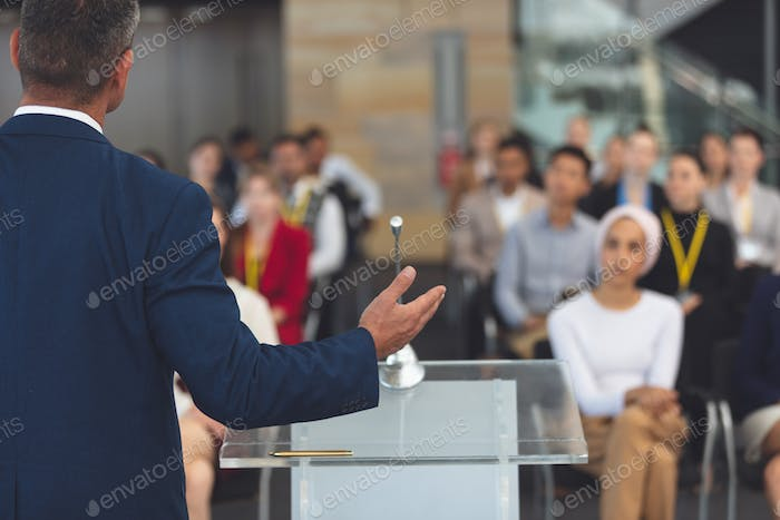 Rear view of mixed race businessman speaking at a business seminar in modern office building
