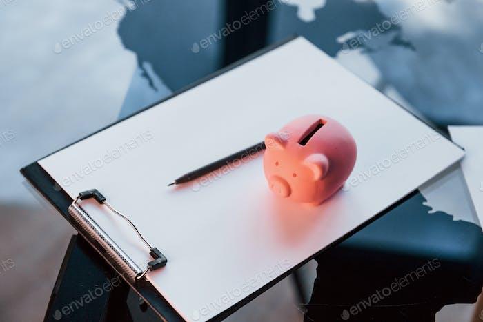 Vista de cerca de la alcancía rosa que se encuentra en el documento blanco sobre la mesa