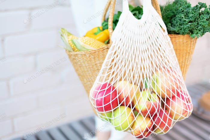 Zero waste concept with copy space. Woman holding straw basket and reusable mesh shopping bag