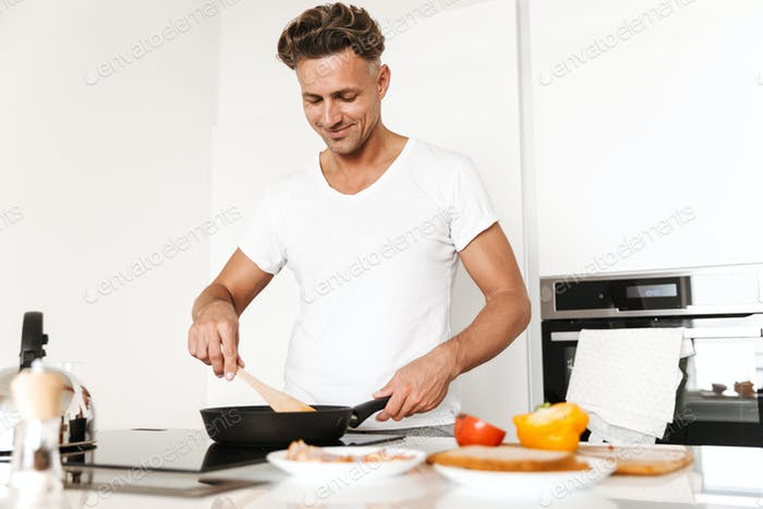 Smiling man cooking eggs for breakfast