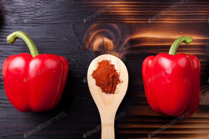 Two sweet red pepper and a wooden spoon with chili powder