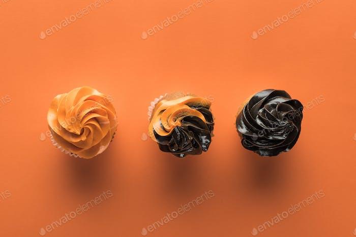 Draufsicht auf köstliche Halloween-Cupcakes auf orangefarbenem Hintergrund