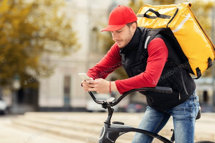 Delivery Guy In Uniform Using Cellphone Sitting On Bike Outdoors