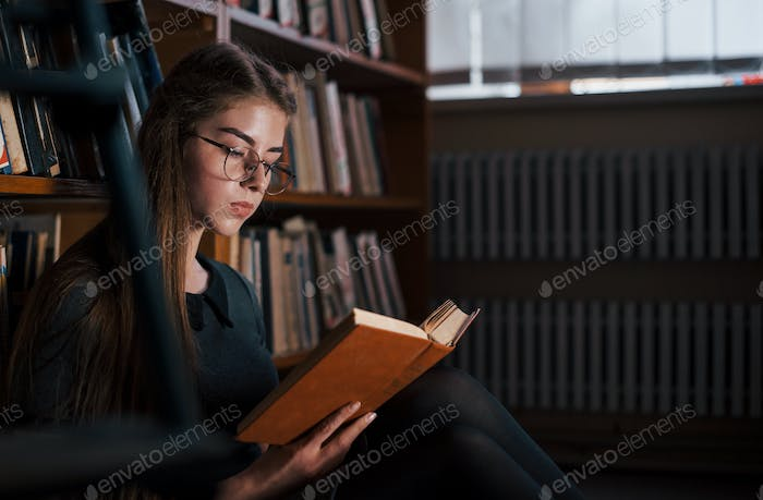 Concentrated at reading. Female student is in library that full of books. Conception of education