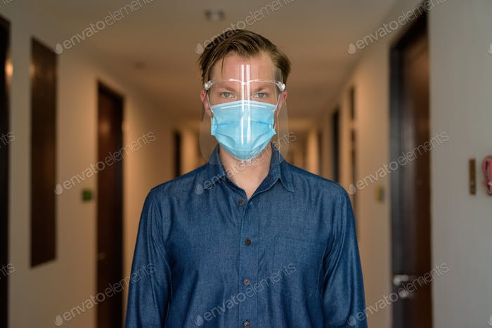 Young man with mask and face shield for protection from corona virus outbreak in the corridor