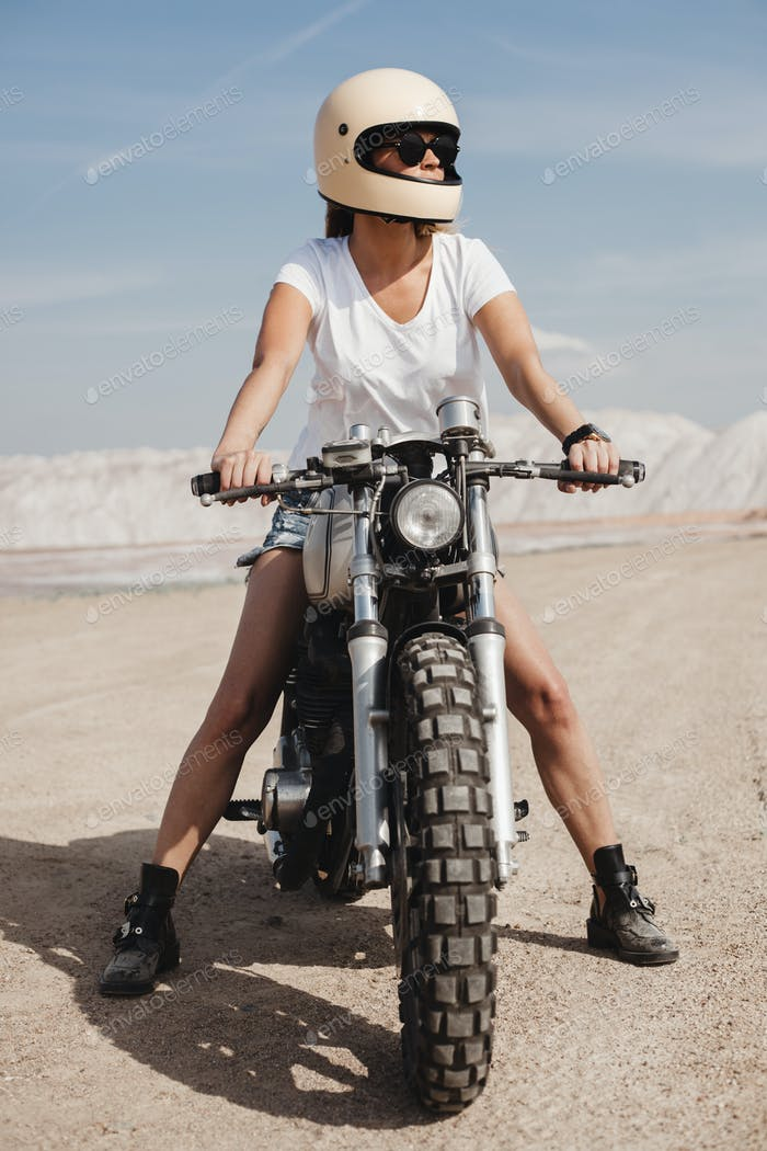 hot daring girl riding motorcycle in the middle of sandy area