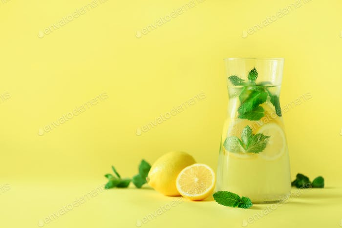Citrus lemonade - cold water with ice, mint, lemon on yellow background. Detox drink. Summer fruit
