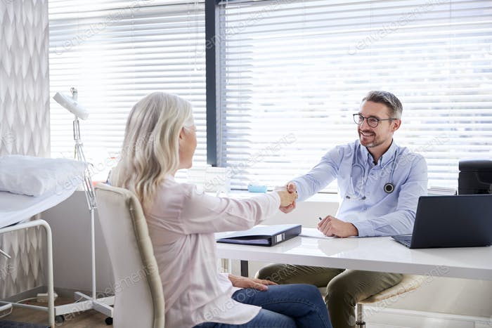 Mature Female Patient Shaking Hands With Doctor Sitting At Desk In Office